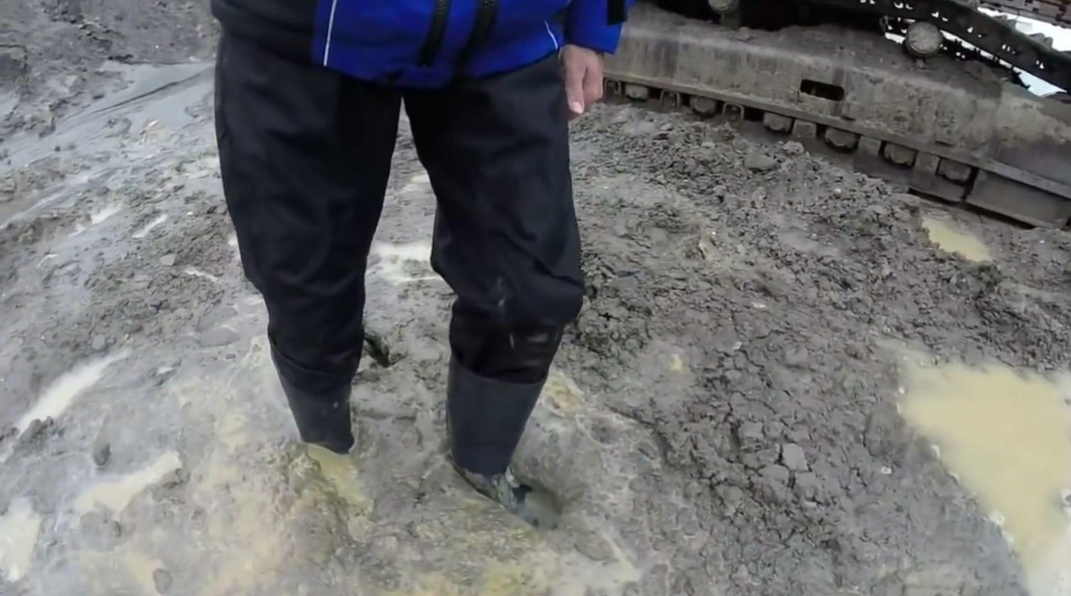 【働く男性の長靴】雨上がりの工事現場を踏みしめる靴底がドロドロに