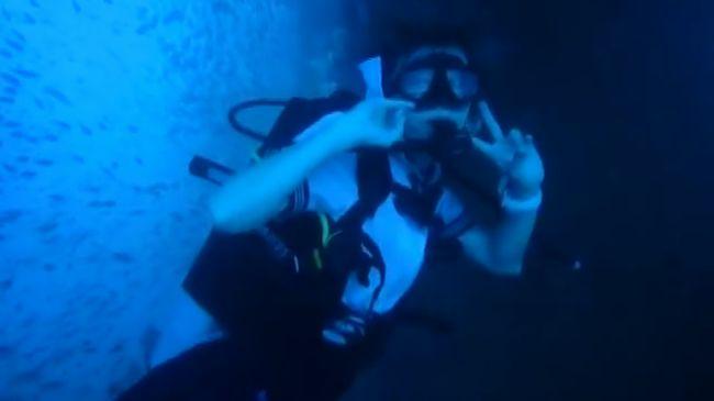 【制服ダイビング】セーラー服姿のダイバーが水中を泳ぎながらピース